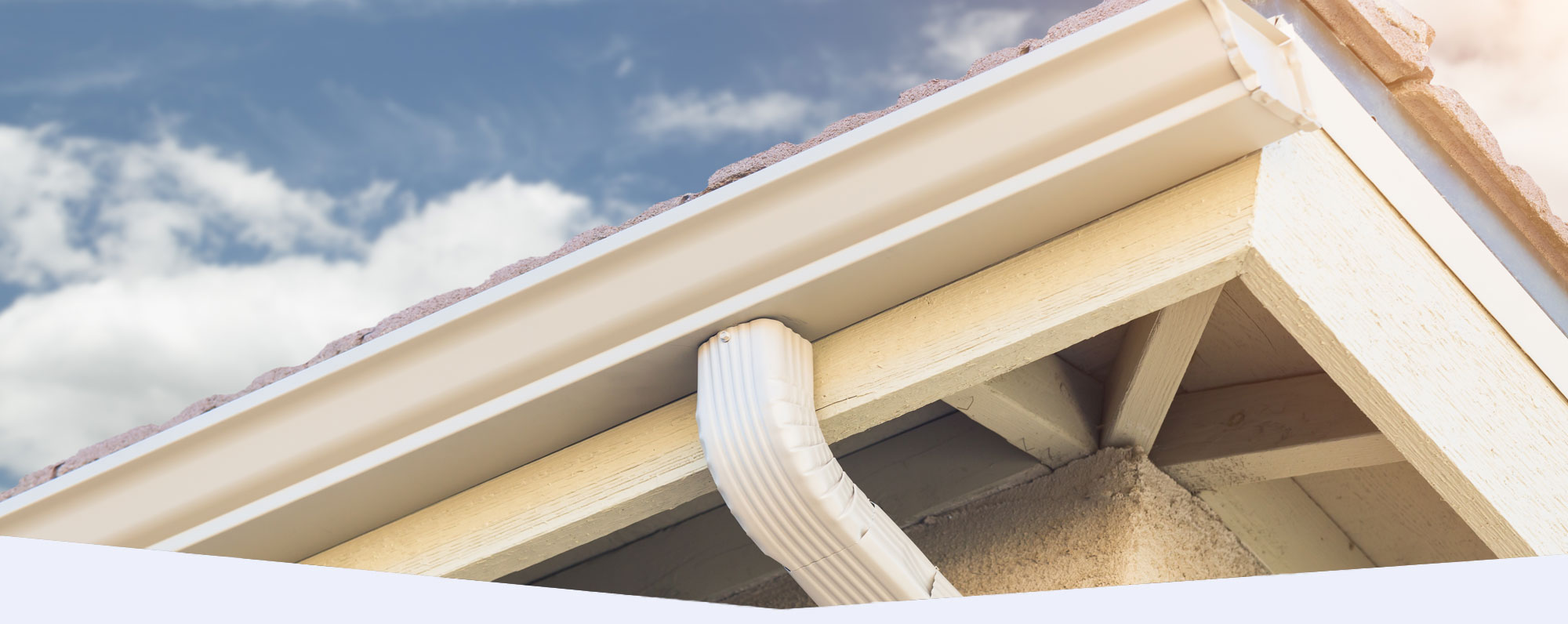 Sky angled shot showcasing a white seamless rain gutter and downspout against a blue sky