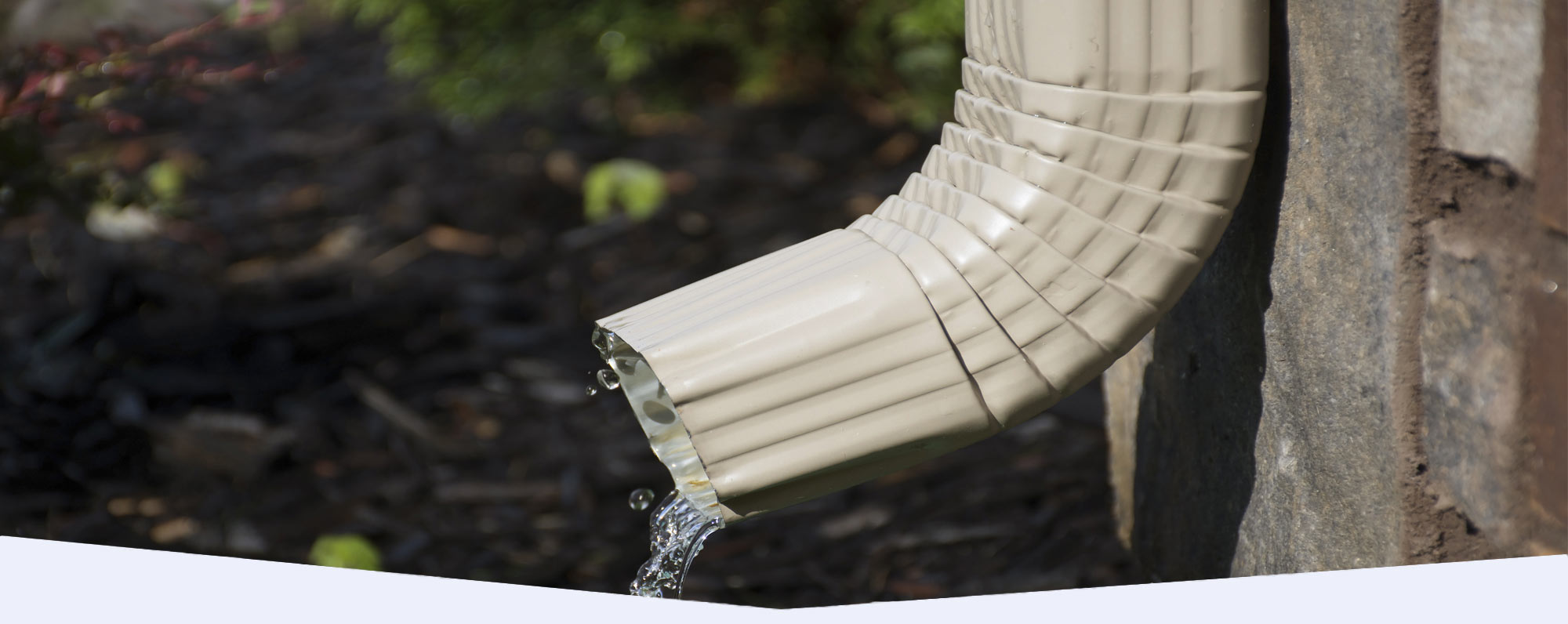 White downspout with rain water pouring out the bottom